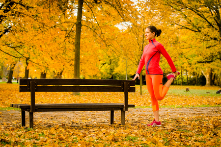 sport training: Young woman warming up at bench before jogging in autumn nature Stock Photo