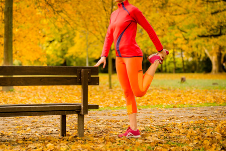 woman stretching: Young woman stretching her leg at bench before jogging in autumn nature
