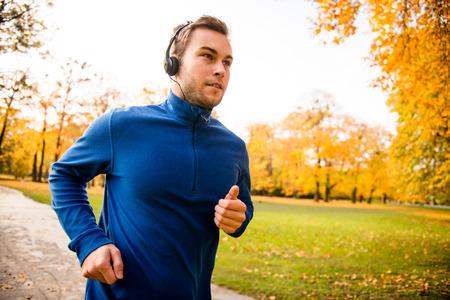 la escucha activa: Hombre joven con los auriculares que se ejecutan en la naturaleza del otoño y escuchar música