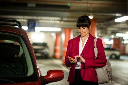 Senior zakenvrouw die naar haar mobiele telefoon kijkt terwijl ze bij haar auto staat Stockfoto