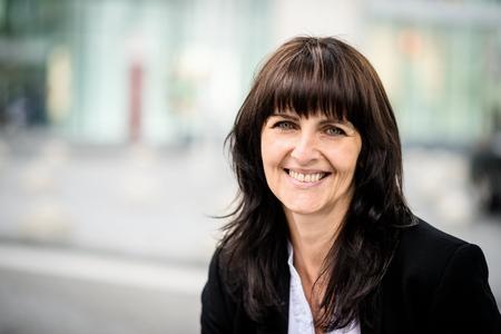 Portret van vertrouwen senior business vrouw met een kantoorgebouw in de achtergrond Stockfoto