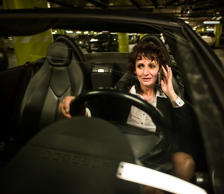 lot of: Senior business woman calling mobile phone in car - night scene, front view