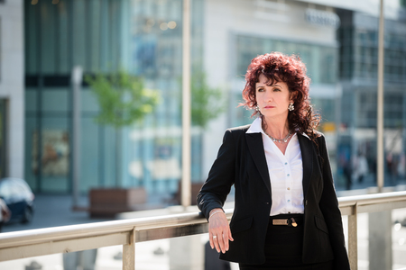 confident business woman: Portrait of confident mature business woman outdoor in modern street