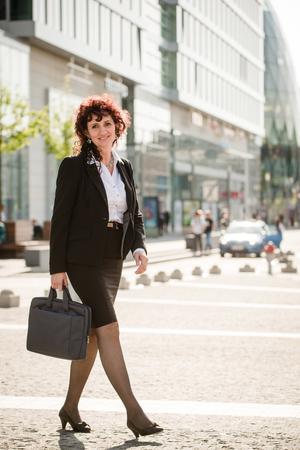 falda: Mujer de negocios mayor que lleva el bolso portátil caminando calle moderna en día soleado