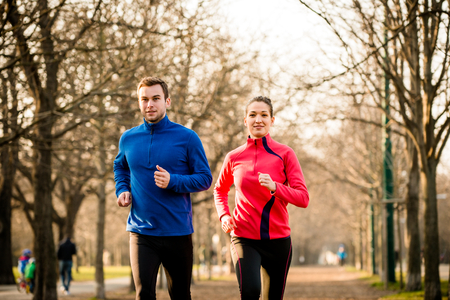 fall: Young couple jogging together in tree alley - late autumn Stock Photo
