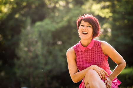 mature women: Portrait of attractive smiling senior woman - sitting outdoor in nature Stock Photo