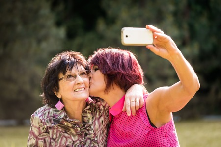 generation: Senior woman is taking selfie with mobile phone while kissing her elderly mother Stock Photo