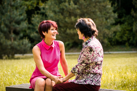 mother on bench: Mature woman talking with her senior mother outdoor on bench