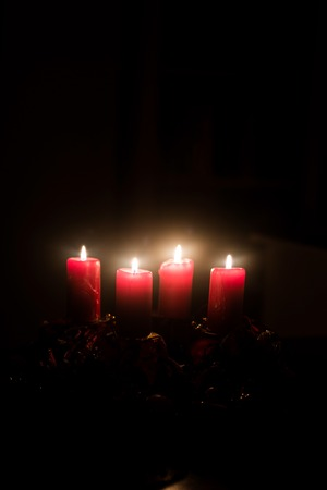 Christmas advent wreath with red burning candles - black background