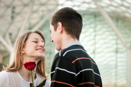 flower rose: Young man handing over a flower (red rose) to woman - outdoor lifestyle scene
