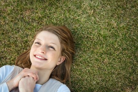 Giovane donna sorridente felice che giace in erba - soprattutto vista con lo spazio della copia