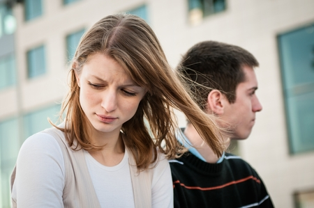 sad couple: Portrait of young woman and man outdoor on street having relationship problems