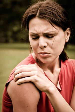 woman in pain: Shoulder injury - sportswoman in pain outdoors in park
