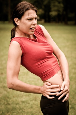 Buttocks injury - sportswoman in pain outdoors in park photo