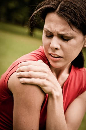 Shoulder injury - sportswoman in pain outdoors in park photo