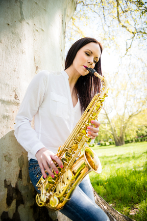 saxophonist: Young woman saxophonist playing saxophone in nature