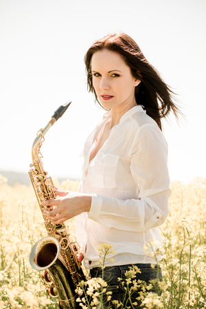 saxophonist: Portrait of young  saxophonist with her saxophone in blossoming rapeseed field