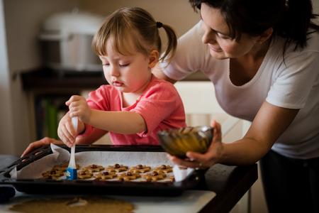 familias felices: Niños hornear galletas junto con su madre - pintura pasteles de miel con la yema de huevo