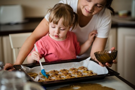 cookie sheet: Mother and child baking together - child spreading yolk on honey cakes