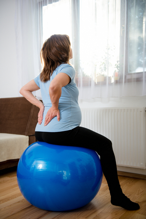 fit ball: Pregnant woman sitting on fit ball with backache at home Stock Photo