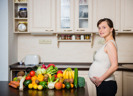 abundance: Pregnant woman with abundance of vegetables and fruits in kitchen