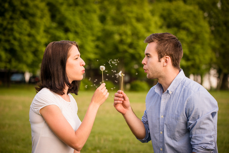 hand free: Young couple blowing out dandelions to each others face