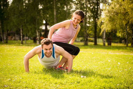 Sport Mann, der Push-ups, während Frau auf ihn als ein Gewicht sitzt Standard-Bild