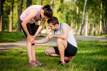 calf pain: Woman helps to man who injured his calf when jogging