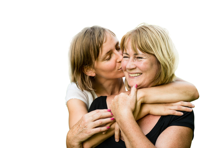 portrait studio: Portrait of happy senior mother kissed by her adult daughter - isolated on white