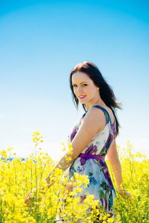 woman in field: Young beautiful woman enjoying life in blossoming rapeseed field