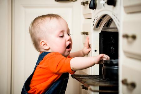 Gevaarlijke situatie - kleine baby open keuken oven