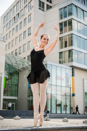 danza clasica: Bailarín de ballet (la bailarina) bailando en la calle con edificios de negocios en el fondo