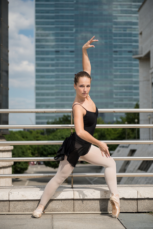 girl shoes: Ballet dancer (ballerina) dancing on street with business buildings in background Stock Photo