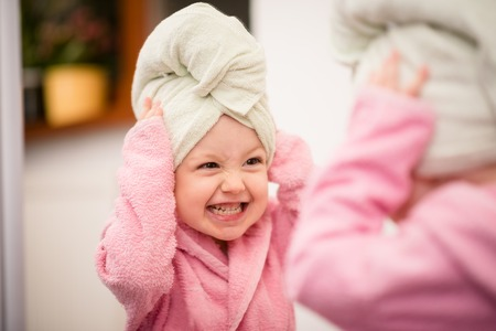 Little child having fun in front of big mirror after bath with towel on head Standard-Bild