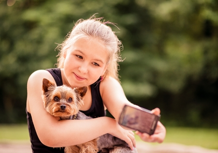 nature photo: Child taking photo of herself and her dog - outdoor in nature Stock Photo