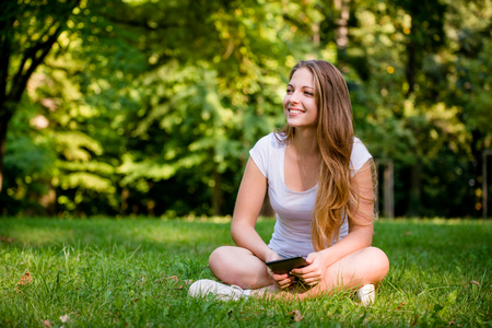 book reader: Young woman (teen girl) reading book on electronic book reader - outdoor in nature