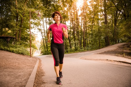 Vitale senior vrouw joggen in het park bij zonsondergang Stockfoto