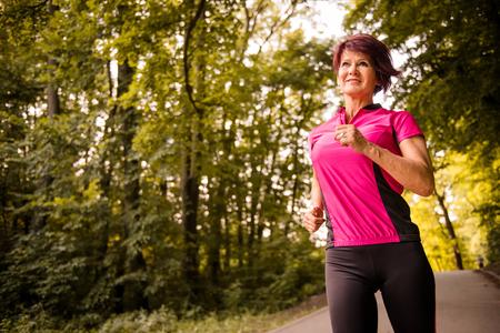 vital: Vital senior woman jogging in park on summer evening