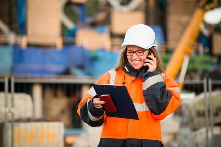 protective workwear: Senior woman engineer wearing protective workwear at work on phone