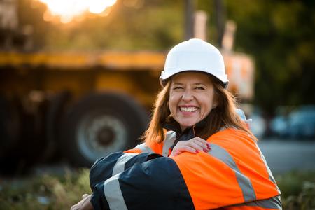 Ingeniero de la mujer mayor que desgasta la ropa de protección en el trabajo - al aire libre al atardecer
