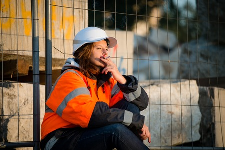senior smoking: Senior woman engineer in protective workwear relaxing during break and smoking cigarette
