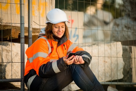 protective workwear: Senior woman engineer in protective workwear relaxing during coffeebreak and looking to phone