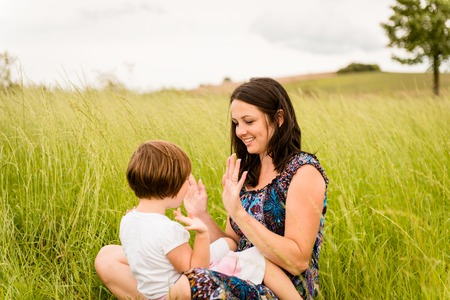 games hand: Clapping hands - mother playing with her daughter outdoor in nature Stock Photo