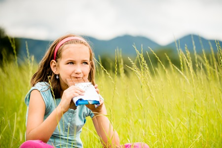 relishing: Child eating and relishing chocolate - outdoor in nature