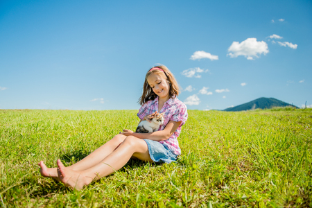 Girl sitting in grass and playing with her cute kitten Stock Photo