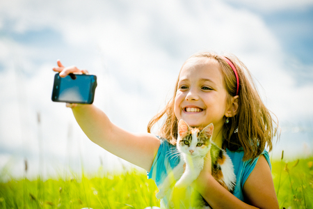 nature photo: Child taking photo with mobile phone camera of herself and her cat - outdoor in nature Stock Photo