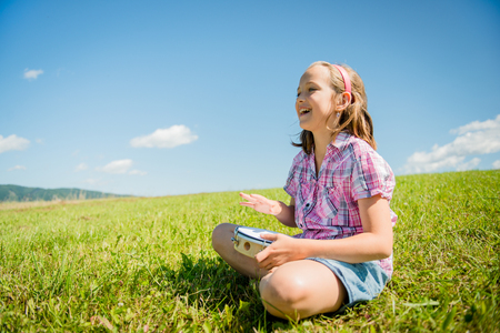 kids outside: Cute teen girl playing tambourine and singing - outdoor in nature Stock Photo