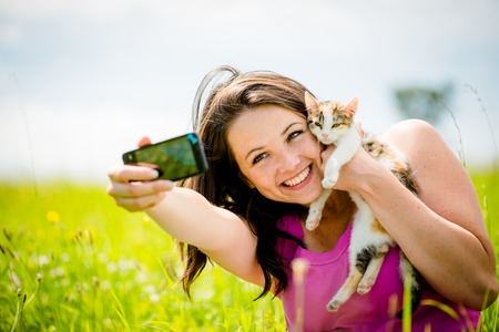 nature photo: Woman taking photo with mobile phone camera of herself and her cat - outdoor in nature