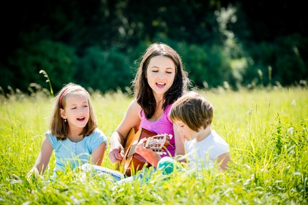 child singing: Woman playing guitar to her children in nature on sunny summer day Stock Photo
