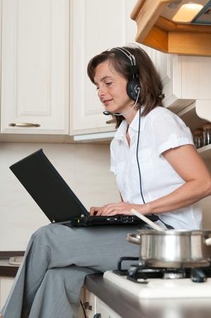 trabajando en casa: Mujer de negocios joven que trabaja desde su casa en la computadora portátil mientras está cocinando comida en la cocina